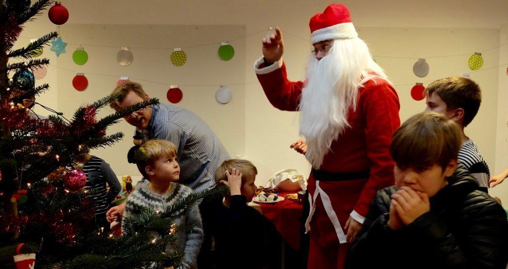 Weihnachtsmann mit Kindergruppe bei Weihnachtsbaum in Island